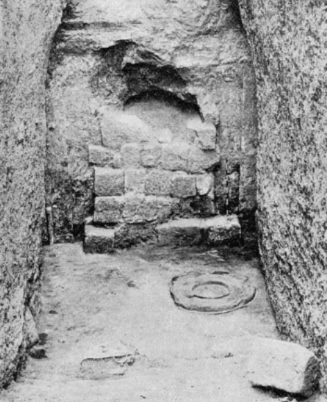 Doorblock of tomb of Aspalta, showing thieves ' entrance above and bronze vessels left on floor at time of burial