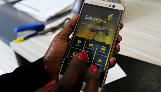 A customer uses her cell-phone to access the Sidian Bank mobile-app inside the banking hall at the Sidian Bank headquarters on the outskirts of Kenya's capital Nairobi
